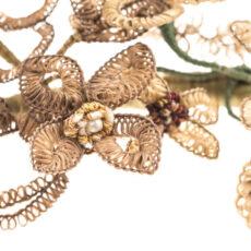 Gros plan de la couronne de cheveux humains tissés autour d'un fil de fer recouvert de ruban vert et décoré de fausses perles et de billes de métal.
