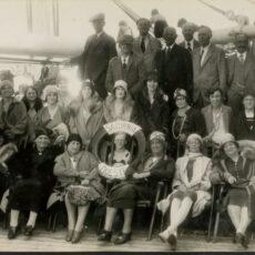 Une photo en noir et blanc montrant trois rangées de gens sur le pont d'un bateau. Les gens sur la première rangée sont assis, et la personne au centre tient une bouée de sauvetage.