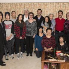Une photo de treize membres de la famille Loy Sing Guen, souriants et décontractés, prise à Noël en 2013. Une table est au premier plan avec, posées dessus, une boîte de chocolats et d'autres friandises du temps des fêtes.
