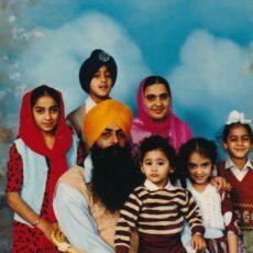 Un portrait photographique d'une famille d'Asie du Sud. Le père et la mère, assis au centre, sont entourés de cinq enfants.