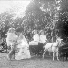 Une photo en noir et blanc de la famille Burns : le père tient les rênes de deux chèvres, attelées à un boghei, où sont assises deux enfants. La mère, deux autres enfants et le chien sont placés juste à côté.
