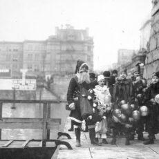 Une photo en noir et blanc du père Noël, sur une digue de l'arrière-port de Victoria, entouré d'un groupe de jeunes garçons déguisés en clowns.