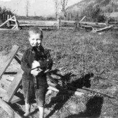 Une photo en noir et blanc d'un petit garçon portant son chaton, pieds nus dans un champ.