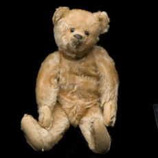 Un ourson en peluche avec un pelage brun pâle, des boutons pour les yeux, un nez fait de cuir et du feutre sous les pattes.
