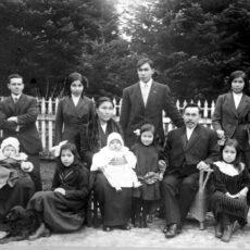 Une photo en noir et blanc d'une famille autochtone nombreuse, dehors dans le jardin, avec leur chien; tous sont vêtus avec cérémonie.