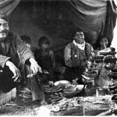 Une photo en noir et blanc d'une famille autochtone, réunie sous une tente, et occupée à fumer des têtes de saumon piquées sur des bâtons au-dessus d'un petit feu.