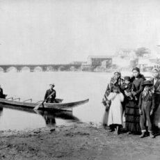 Une famille autochtone. Quatre femmes et quatre enfants sont debout sur un rivage boueux, alors que deux hommes sont assis dans un canoë de bois dans le port. Au loin, on aperçoit un pont et des bâtiments en bois.