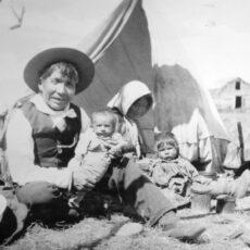 Une photo en noir et blanc d'un homme autochtone assis par terre et tenant un bébé. Une femme est assise à côté de lui avec un jeune enfant sur les genoux.