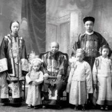 Un portrait photographique de la famille de Lee Mong Kow en vêtements traditionnels. Une dame âgée, entourée de trois jeunes enfants, est assise au centre; debout derrière, se trouvent un jeune homme et une jeune femme.