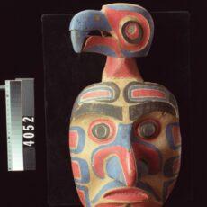 Un masque de bois sculpté représentant un visage humain auquel se rattache une tête d'oiseau. Le masque est peint en rouge et noir.