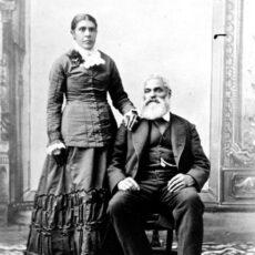 Un portrait photographique en noir et blanc d'une femme debout, et de son mari assis. Tous deux sont vêtus cérémonieusement.