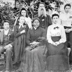 Une photo en noir et blanc d'une famille assise à l'extérieur. Une femme âgée, vêtue d'une robe foncée, est assise au centre. Derrière elle se tient un homme âgé, portant une barbe très fournie. Le couple est entouré de cinq jeunes : un adolescent et son chien, deux jeunes filles et deux jeunes femmes.