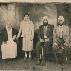 Un portrait photographique en noir et blanc d'une famille de l'Asie du Sud. Une dame âgée, portant un long vêtement blanc et un manteau foncé, est assise à droite. Près d'elle se tient une jeune femme vêtue d'une jupe et d'un manteau léger. Deux hommes, portant complets et turbans, sont assis à droite.