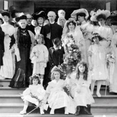 Une photo en noir et blanc du mariage célébré en 1905. Les mariés sont au centre d'un large groupe composé d'amis et de membres de la famille.