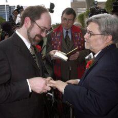 Une image de deux hommes, s'échangeant anneaux et vœux de mariage. Un pasteur de la United Church est debout entre les deux hommes et tient un livre.