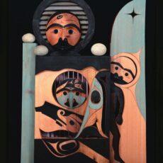 Une sculpture sur cèdre, peinte, qui représente l'oiseau-tonnerre, originaire du territoire Mowachaht, une nageoire et une queue d'épaulard (Orque), la lune du solstice d'hiver, les montagnes, un canoë, et une des figures mythiques qui a transmis le savoir au peuple Nuu-chah-nulth.