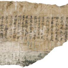 Un grand fragment de plâtre, découpé à même un mur; on y distingue des caractères chinois.