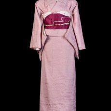 Un kimono de femme en soie rose pâle avec sa ceinture rose foncé.
