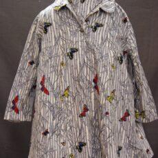 Un vêtement de maternité, taillé dans un tissu à motifs de papillons colorés qui volent à travers du bambou gris et blanc.
