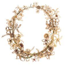 Une couronne de cheveux humains, tissés autour d'un fil de fer recouvert de ruban vert et décoré de fausses perles et de billes de métal.