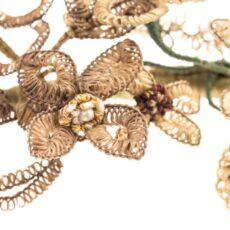 Gros plan de la couronne de cheveux humains tissés autour d'un fil de fer. Le fil de fer est recouvert de ruban vert et décoré de fausses perles et de billes de métal.