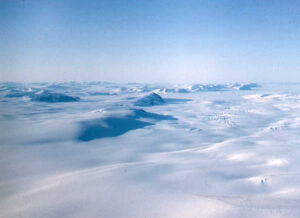 Blue sky above frozen mountain tops covered with snow and ice.