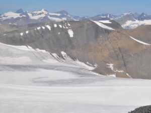 Icy top of a glacier looking out towards other ice capped mountains. Blue sky in the distance.