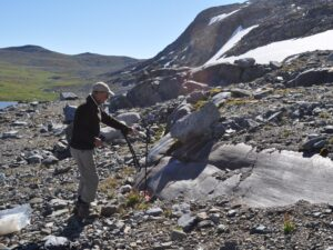Up on a mountain, a man stands in front of a rock smoothed by glaciers.