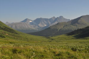 A green tundra slope surrounded by mountains.