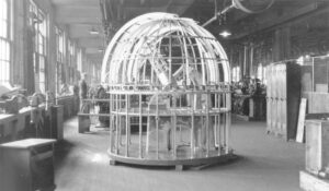 Scale model of the Plaskett Telescope in a dome (without outer covering). Factory workers and various equipment in the background.