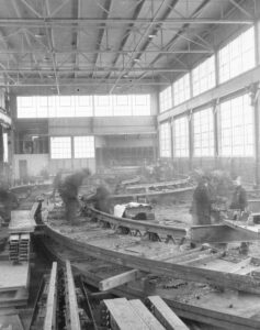 Workers construct sections of railway tracks. Steel and boards in piles on factory floor.