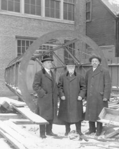 Three men wearing heavy coats in front of telescope tube. There is snow on the ground.
