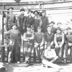 Seven workmen stand and six workmen sit on a ladder. Topp, also in work clothes, stands at a slight distance from the workers.