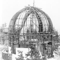 Steel framework of the dome without outer covering. A crane, the pier and a water tower are in the background.