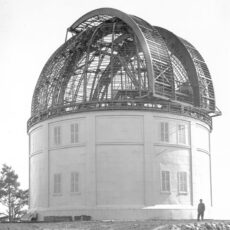 The steel structure of the dome, without its outer covering, and the completed lower half of the observatory. A man in a suit stands in front of the building.