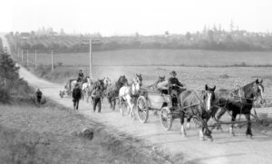 Two carts, ten horses and five men haul equipment along a dirt road. Farmland and rolling hills in the background.