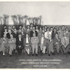A large group of astrophysicists posing in a field. Four female and thirty male astrophysicists in 1950s suits are arranged in rows. Text on the photo reads: National Science Foundation Binary Star Conference, Dominion Astrophysical Observatory, Victoria, BC, August 16 to 18, 1956.