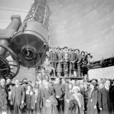 Group photograph around the Plaskett Telescope. Adults and children stand around the base of the telescope.