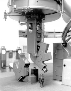 Close-up view of the spectrograph and associated instruments at the bottom of the Plaskett Telescope. Wall-mounted clocks in the background.