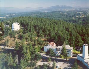 Aerial view of the DAO complex including several office buildings and the observatory, surrounded by evergreen trees.