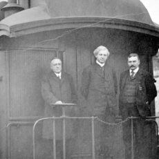 Three men dressed in suits pose for the camera during an election campaign, standing on the caboose of a train.