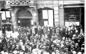 A large crowd stands waiting on the street in front of buildings on Government Street in Victoria BC. Long lists of paper are posted on the windows of the building. The crowd is mostly men wearing hats and suits. A few men in soldier's uniforms are visible as are a few women.