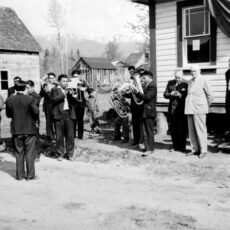 On the left side of the photograph, a group of roughly ten First Nations men play brass instruments outside a building. On the right hand side of the photograph men in suits, stand listening.