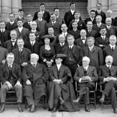 A large group of people standing in rows on the steps of the BC Provincial Legislature building. Most are white men in suits. One woman stands in the centre of the second row. She is wearing a large hat and a dark dress.