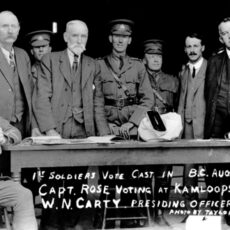 "Nine men gather around a table in a doorway. Two men in World War I uniforms are sitting at either end of the table. Some handwriting at the bottom of the photograph reads ""1st soldiers vote cast in B.C. Aug. 17, '16; Captain Rose voting at Kamloops; W.N. Carty, presiding officer. Photo by Taylor."""