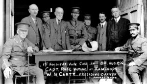 """Nine men gather around a table in a doorway. Two men in World War I uniforms are sitting at either end of the table. Some handwriting at the bottom of the photograph reads """"1st soldiers vote cast in B.C. Aug. 17, '16; Captain Rose voting at Kamloops; W.N. Carty, presiding officer. Photo by Taylor."""""""