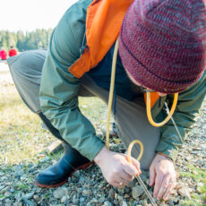 A researcher kneels down and uses a tube to capture insects among small rocks.