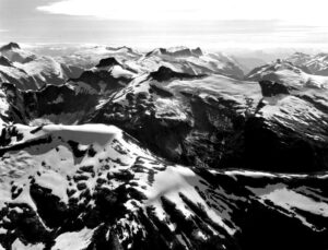 Black and white image of snow-covered mountains from above.