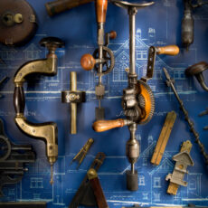 A variety of tools, including a hammer and hand drills with a blue print of a house in the background.