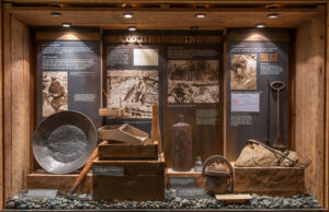 A display case full of gold-panning tools such as rakes and a dented metal pan.